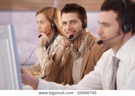 Cheerful young male dispatcher working in callcenter, smiling.?