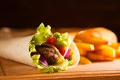 Tasty Fresh Wrap Sandwich With Beef And Vegetables, On Wood Table poster