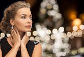 jewelry, holidays, luxury and people concept - beautiful woman in black wearing earrings over christ poster