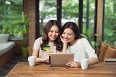Two Asian Woman Using Laptop For Shopping Online With Credit Card Payment poster