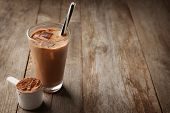Glass with protein shake and powder in scoop on wooden table poster