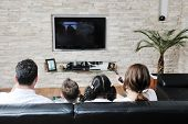 stock photo of watching movie  - happy young family wathching flat tv at modern home indoor - JPG