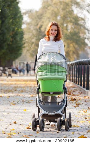 Happy young mother with baby in buggy walking in autumn park
