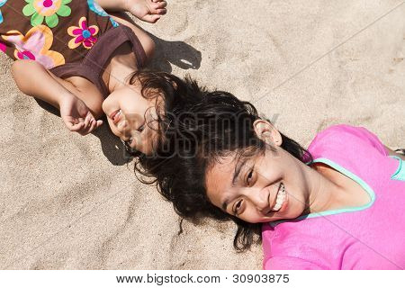 Ethnic Mother And Child Lay Down On Beach Sand