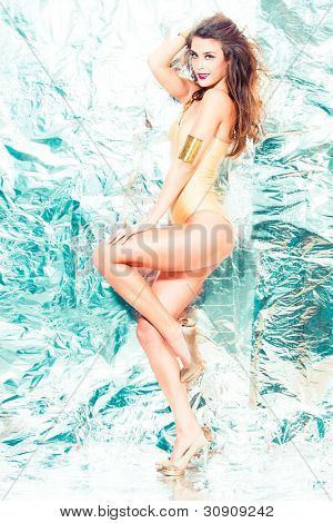 smiling fashion model in one piece swimwear golden color, stand  in front  shiny background, full body shot