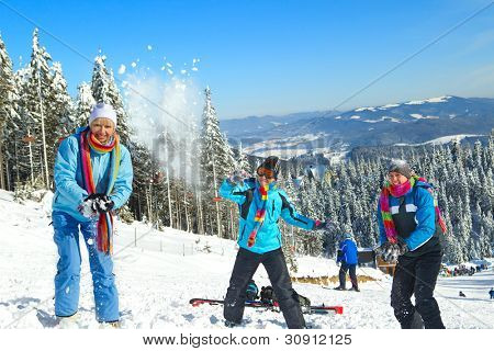 Guys having snowball fight with girl in snow in winter background
