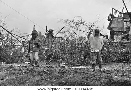 Unidentified kids walk in mud through the Nairobi slum