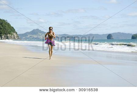 woman jogging along a beautiful beach.