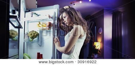 Young woman looking at fridge