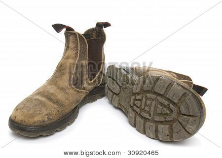 Old pair of dirty working boots on white background