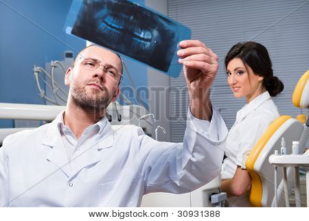 Dentist With X-ray And Smiling Patient In The Background
