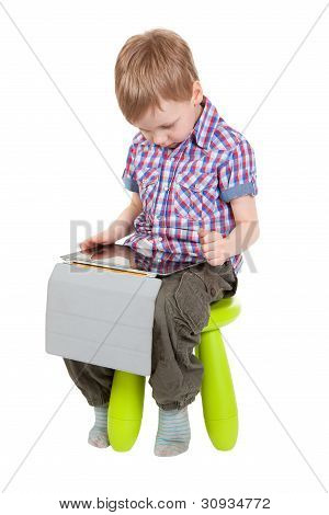 Boy With A Tablet Pc Sitting On A Chair