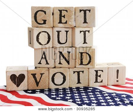 "Rustic alphabet blocks arranged to say, ""Get out and Vote!"" sitting on a bed of stars and stripes.  On a white background."
