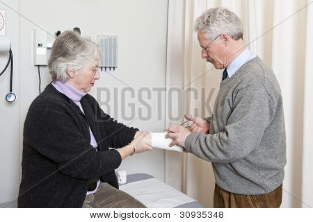 Doctor cutting off the bandage on an elderly woman's arm with scissors in a general medical practice