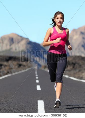 Jogging woman running. Female runner during outdoor workout in beautiful mountain nature landscape. Beautiful young mixed race fit fitness model training for marathon.