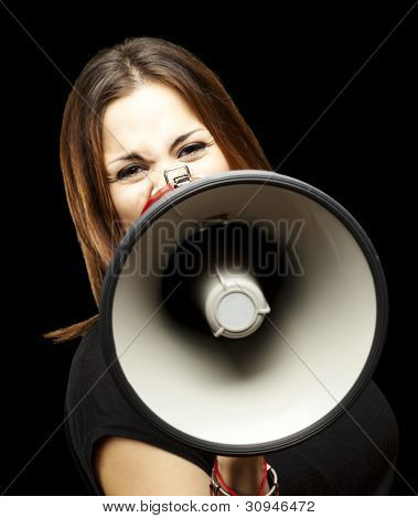 portrait of a young woman shouting with a megaphone over a black background