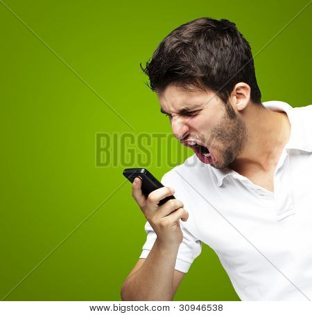 portrait of an angry young man shouting using a mobile over a green background