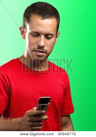young man typing on a mobile phone on a green background
