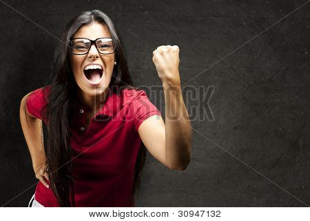 portrait of a young woman gesturing victory against a grunge wall