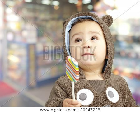 portrait of a handsome kid wearing a brown bear sweatshirt holding candy against a candy shop background