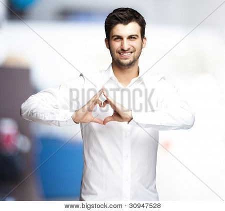portrait of a young man doing a heart symbol against an indoor background