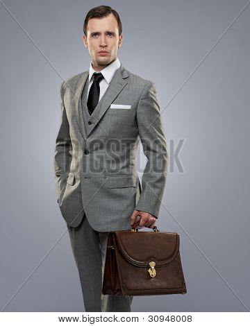 Empresario con un maletín aislado en gris.