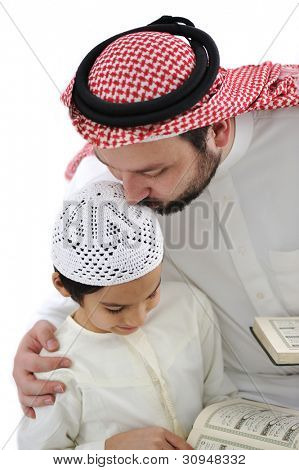 Middle eastern education, father kissing son while reading Koran