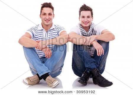 two men friends looking very happy, sitting next to each other on white background