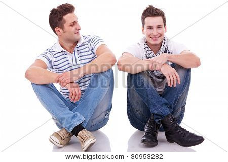 two casual men sitting on a white background. one looking at the camera and the other looking at his friend