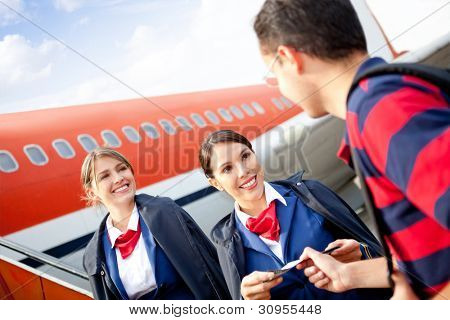 Friendly flight attendants welcoming passenger into the airplane
