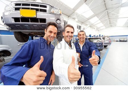 Happy group of mechanics with thumbs up at a car garage