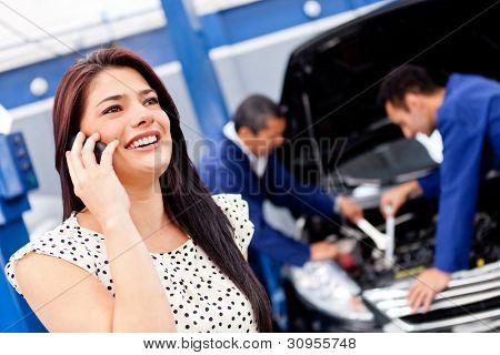 Woman calling mechanic after her car broke down