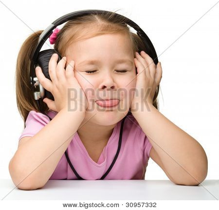 Cute little girl enjoying music using headphones and showing her tongue, isolated over white