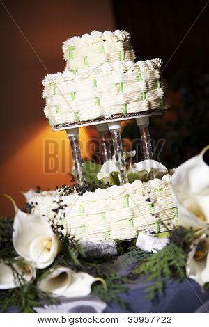 Wedding cake on a table with candles and white flowers, focus is on the cake, orange colored lights behind