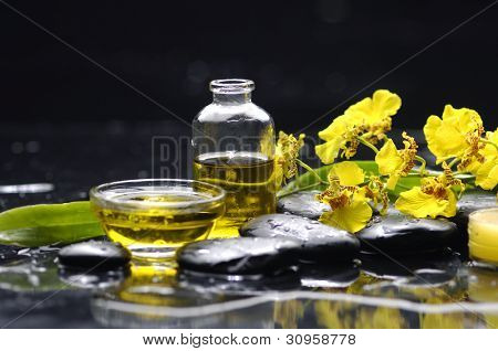 Spa still life with bottle of essential oil and branch yellow orchid