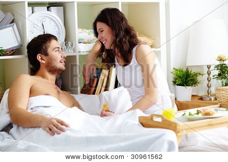 A young man and his girlfriend sitting in bed and talking in the morning