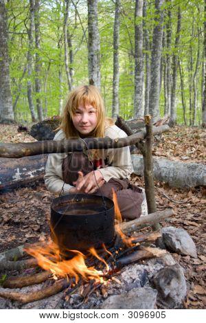 Girl Sitting Near Of Bonfire In Forest