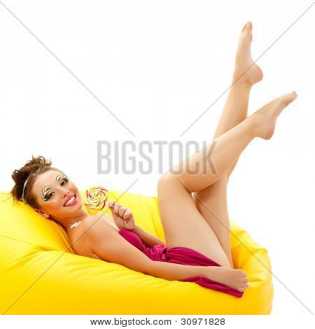 portrait of young smiling woman with beautiful make-up holding sweet candy lying on yellow sofa isolated on white background