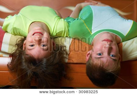Two smiling kids lying in bed