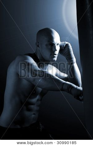 Portrait of a muscular male kick boxing - lowkey shot, selective focus