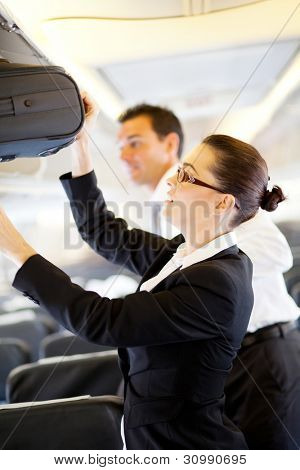 friendly flight attendant helping passenger with carry on luggage