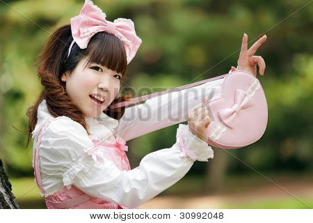 japanese woman in sweet lolita cosplay showing heart bag