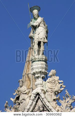 Vertical oriented image of statues on the rooftop of San Marco Basilica against blue sky in Venice, Italy.