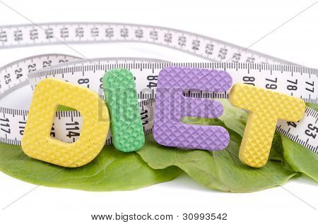 Rubber letters make word diet on the fresh green lettuce and centimeter tape, isolated on white