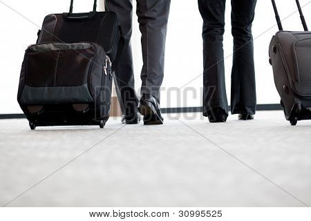 business travellers walking ain airport with luggage