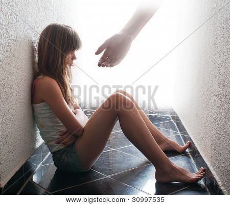 Depressed teenager sitting on the floor while hand coming out from bright background offers support