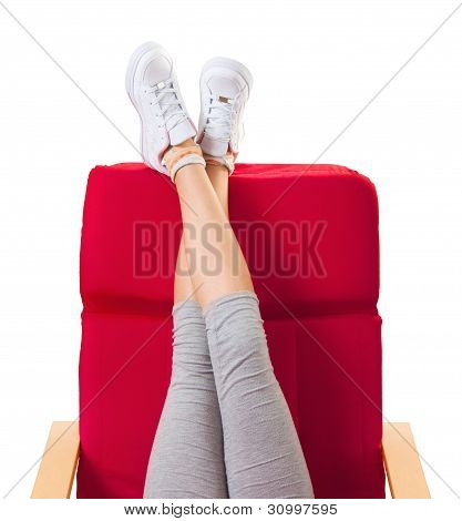 Girl resting in the red chair with her legs up in the air