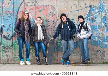 Happy teenage friends with school bags and skateboards standing in front of the graffiti wall