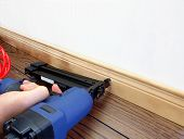 pic of baseboard  - Male hand with carpenter tool installing baseboard - JPG