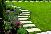 Back Yard With A Marble Stone Walkway Of Square Tiles Near A Green Meadow With A Flower Bed, Garden  poster